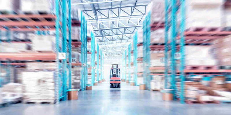 warehouse metal structure interior with  forklift truck in selective focus, rows of merchandise shelves with goods container boxes